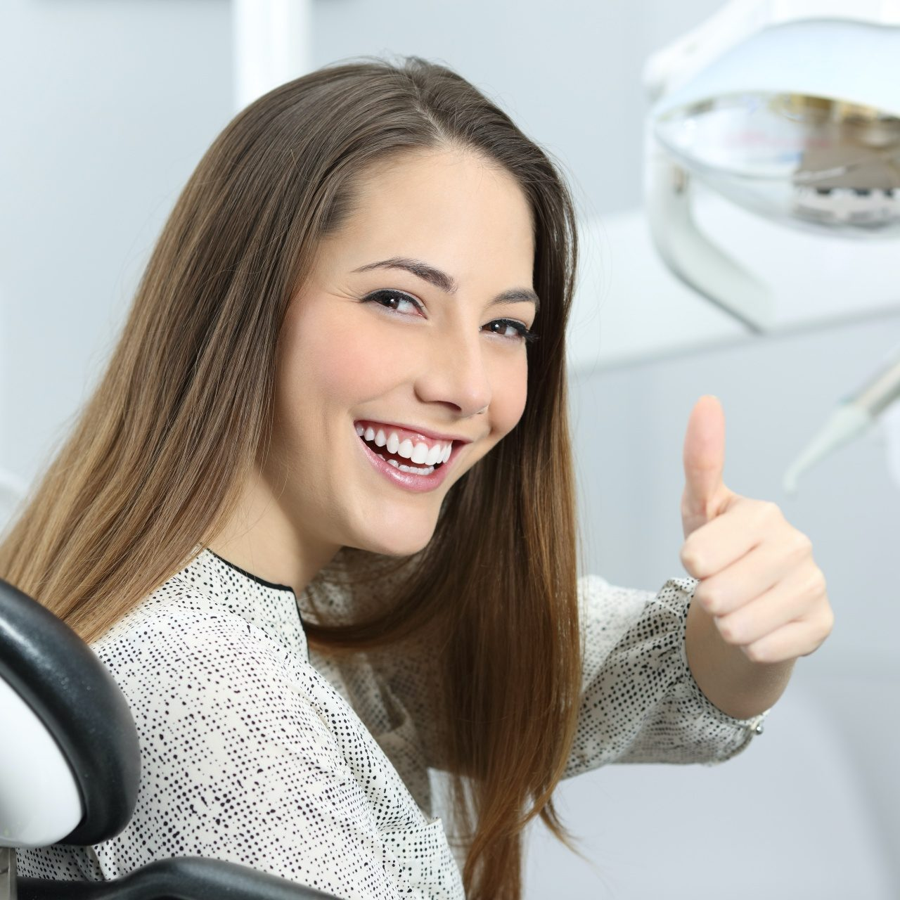Woman smiling and giving a thumbs up in a dentist chair